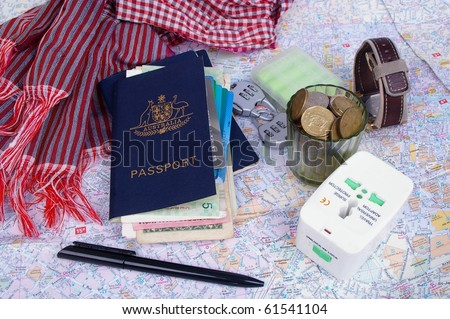 australian passport and holder with travel items on top of paris map - stock photo