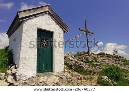 Austria, Tyrolean alps, small chapel an a wooden mountain cross - stock photo