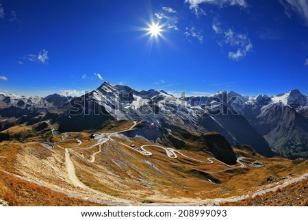 Austrian Alps. Excursion to the picturesque panoramic way Grossgloknershtrasse. Sunny day in early autumn. Great highway winds between hillsides yellowed - stock photo