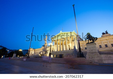 Austrian Parliament Building and The Athena Fountain at night. - stock photo