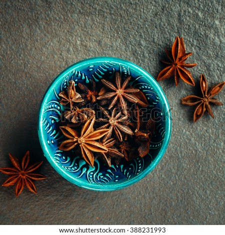 Authentic Blue Bowl Full of Anise Stars. Spice Background. Top View. Image Toned. - stock photo