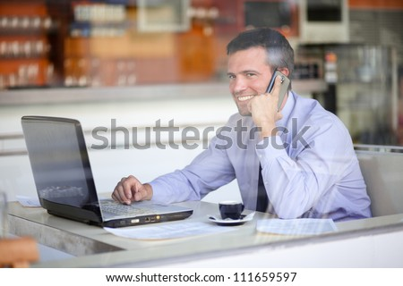 Authentic image of a businessman working in a cafe - stock photo