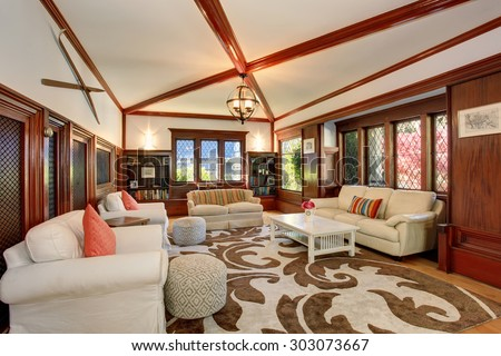Authentic living room with brown and white decorative rug, also including hardwood flor and white sofas. - stock photo