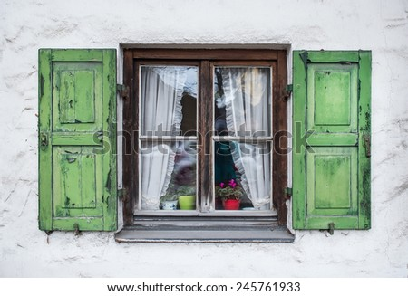 Authentic window with green wooden shutters in a small town of Garmisch-Partenkirchen in Bavarian Alps, Germany - stock photo