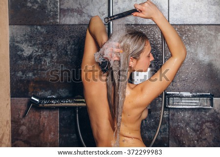 Autiful woman standing at the shower. is washing her hair. - stock photo