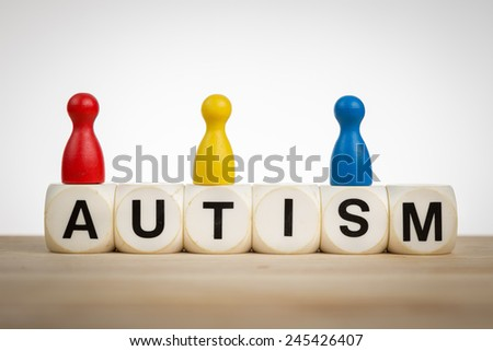 Autism concept: Pawns in different colors on top of toy dice - stock photo