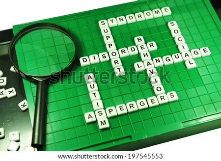 Autism concept with game board and magnifying glass - stock photo