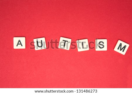 Autism spelled out in plastic letter pieces on red background - stock photo
