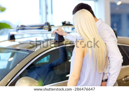 auto business, car sale, consumerism and people concept - couple buying car in auto show or salon from back - stock photo