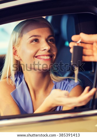 auto business, car sale, consumerism and people concept - happy woman taking car key from dealer in auto show or salon - stock photo