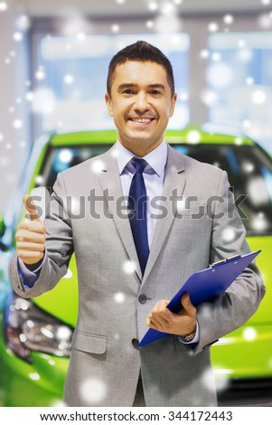 auto business, car sale, consumerism, gesture and people concept - happy man showing thumbs up at auto show or salon over snow effect - stock photo