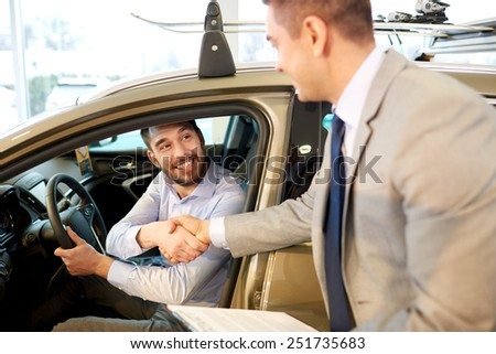 auto business, car sale, consumerism, gesture and people concept - happy man with car dealer making deal and shaking hands in auto show or salon - stock photo