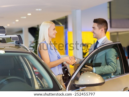 auto business, car sale, consumerism, gesture and people concept - happy woman with car dealer making deal and shaking hands in auto show or salon - stock photo