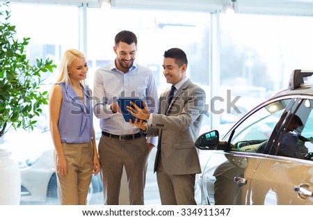 auto business, car sale, technology and people concept - happy couple with car dealer in auto show or salon - stock photo