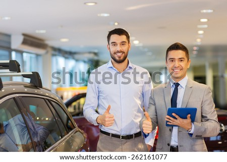 auto business, car sale, technology, gesture and people concept - happy man and car dealer with tablet pc computer showing thumbs up in auto show or salon - stock photo
