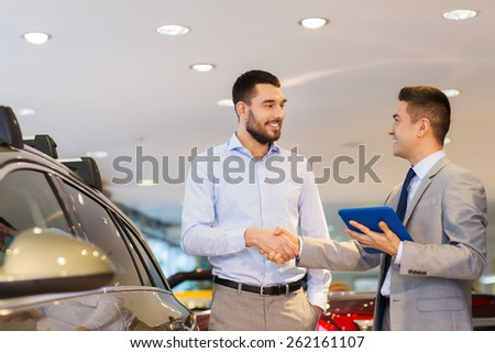 auto business, car sale, technology, gesture and people concept - happy man and car dealer with tablet pc computer shaking hands in auto show or salon - stock photo