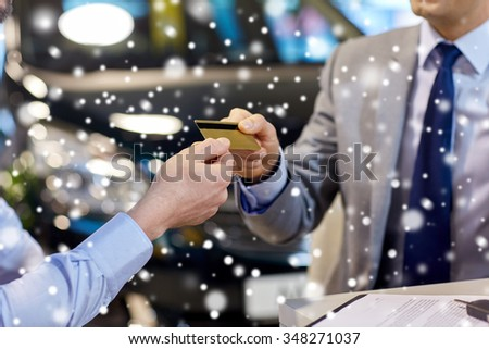 auto business, sale and people concept - close up of customer giving credit card to car dealer in auto show or salon over snow effect - stock photo