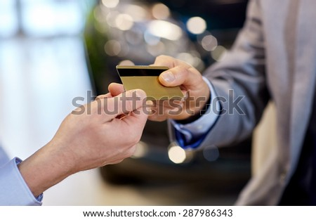 auto business, sale and people concept - close up of customer hand giving credit card to car dealer in auto show or salon - stock photo