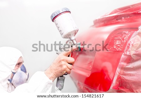 auto engineer painting a red paint on modern car in special booth - stock photo