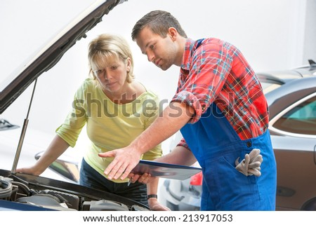 Auto mechanic and female customer in auto repair shop - stock photo