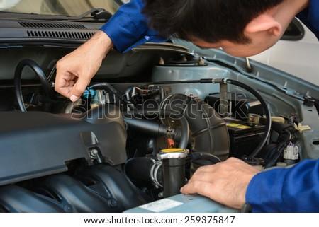 Auto mechanic checking car engine - hand focused - stock photo