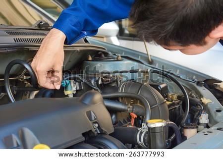 Auto mechanic checking car engine - soft focus - stock photo