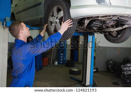 Auto mechanic examining car tire in garage - stock photo