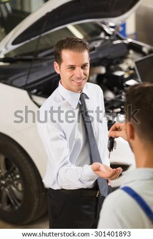 Auto mechanic giving his car key at customer. - stock photo