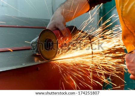 auto mechanic grinding metal on a metal surface  - stock photo