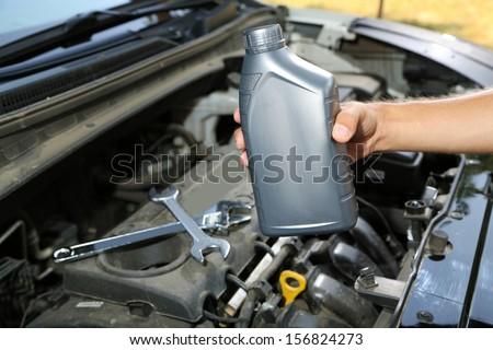 Auto mechanic hand holding motor oil  - stock photo