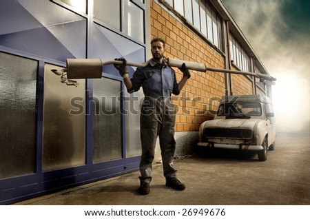 auto mechanic holding a silencer outside the garage - stock photo