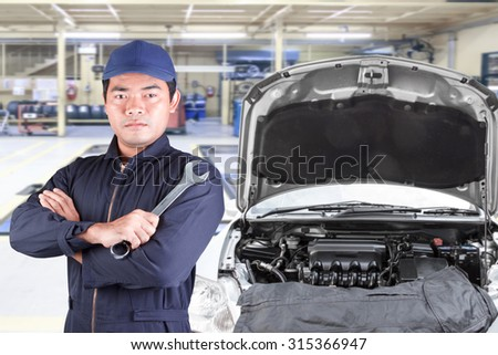 Auto mechanic holding wrench at maintenance repair service station - stock photo
