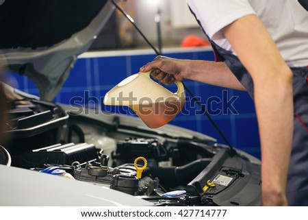 Auto mechanic is changing motor oil into a engine at car station - stock photo