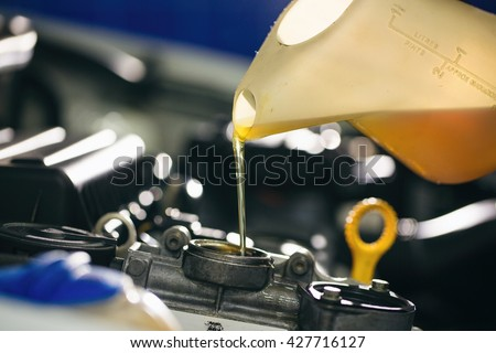 Auto mechanic is changing motor oil into a engine at car station. Close up - stock photo