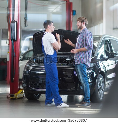 Auto mechanic talking with client in repair garage - stock photo