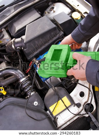 Auto mechanic testing the electrical system on automobile - stock photo