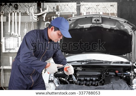 Auto mechanic use tool operation repaired engine at maintenance repair service station with tools background - stock photo