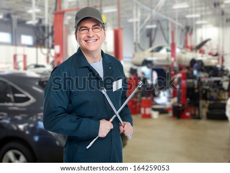Auto mechanic with wrench. Car repair service. - stock photo