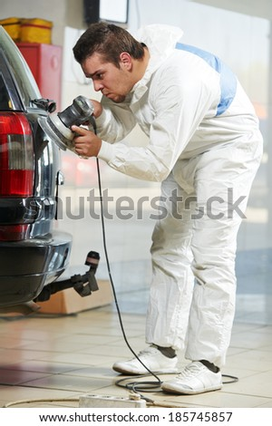 auto mechanic worker polishing car at automobile repair and renew service station shop by power buffer machine - stock photo