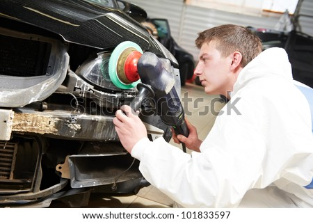 auto mechanic worker polishing car headlight at automobile repair and renew service station shop - stock photo