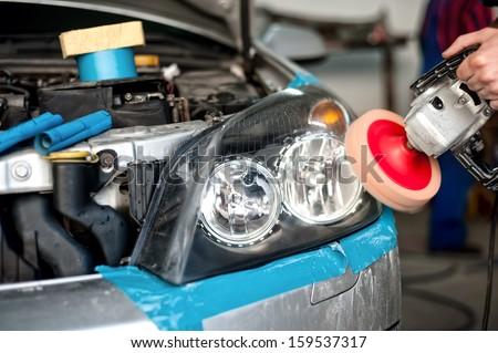 auto mechanic working on polishing a car headlight with power buffer machine in car care system - stock photo