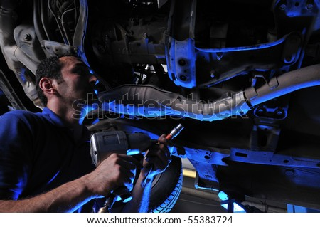 Auto mechanic working under dramatically lightened car - a series of MECHANIC related images. - stock photo