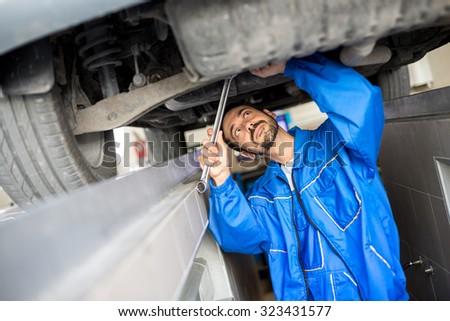 Auto mechanic working under the car - stock photo