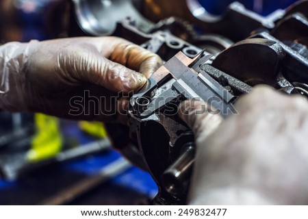 Auto mechanical carefully measures the desired part - stock photo