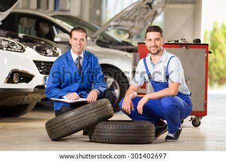 Auto mechanics posing at camera with tire. - stock photo