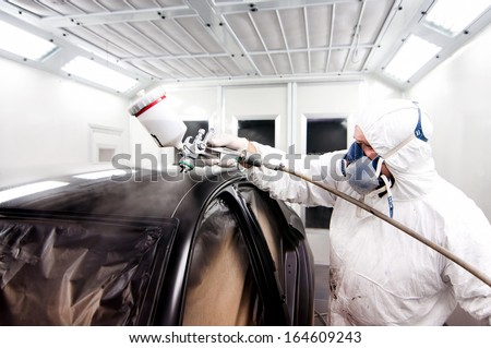 Auto painter spraying a car body with black paint and protective gear - stock photo
