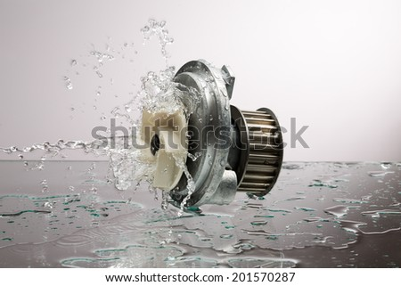 Auto parts, engine cooling pump in water splash on gray gradient background - stock photo