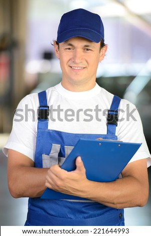 Auto repair service. Portrait of handsome smiling mechanic man - stock photo