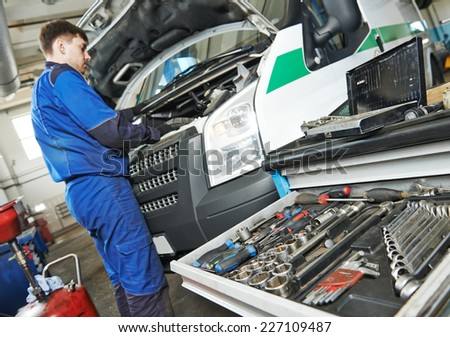 auto repairman industry mechanic worker servicing car auto in repair or maintenance shop service station - stock photo