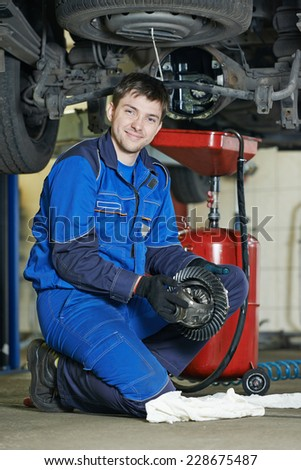 auto repairman mechanic portrait with axle reduction gear in car auto repair or maintenance shop service station - stock photo